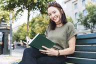 Portrait of smiling young woman sitting on bench with a book - WPEF02208