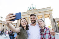 Portrait of three happy friends taking selfie with cell phone in front of Brandenburger Tor, Berlin, Germany - WPEF02214