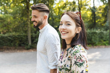Portrait of happy young couple walking in a park - WPEF02226