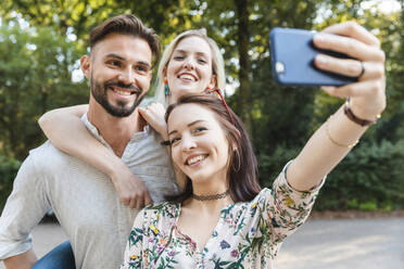 Group of three friends taking selfie with smartphone - WPEF02232