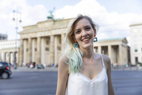Portrait of smiling young woman in front of Brandenburger Tor, Berlin, Germany - WPEF02235