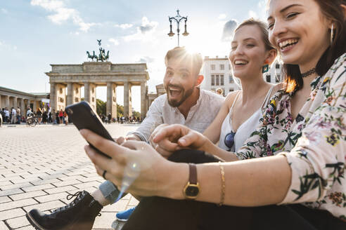 Three laughing friends sitting near Brandenburger Tor looking at smartphone, Berlin, Germany - WPEF02241