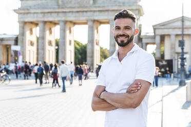 Portrait of smiling young man standing in front of Brandenburger Tor, Berlin, Germany - WPEF02244