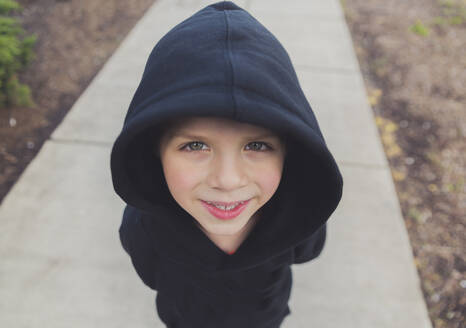 High angle portrait of happy boy wearing black hooded jacket while standing on footpath - CAVF66663