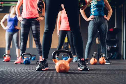 Women training in gym, standing by kettle bells, surface level - CUF52913