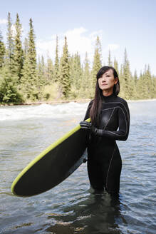 Portrait confident female surfer with surfboard in river - HEROF39638