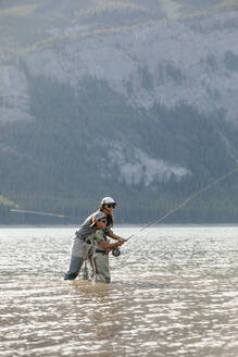Mother and son fly fishing in sunny lake - HEROF39683