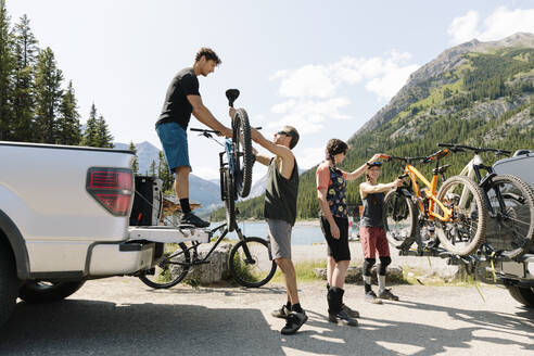 Friends unloading mountain bikes from pickup truck at sunny lakeside - HEROF39728