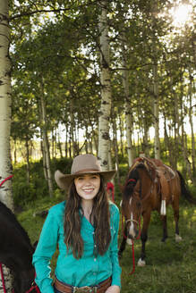 Young woman smiling towards camera with horse in woods - HEROF39968