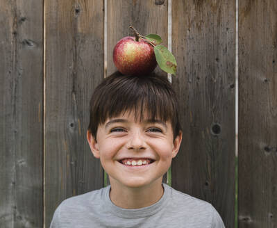 Boy smiling while balancing an apple on his head against wooden fence - CAVF66938