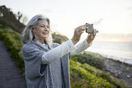 Side view of cheerful senior woman photographing with smart phone at Manhattan Beach during sunset - CAVF67127