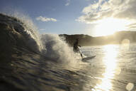 Surfer on a wave at sunset time - CAVF67337