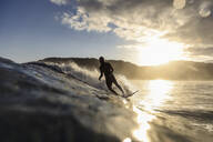 Surfer on a wave at sunset time - CAVF67340