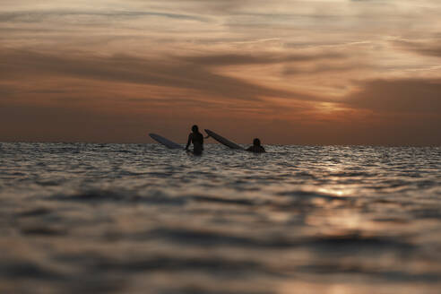 Surfers in ocean at sunset - CAVF67615