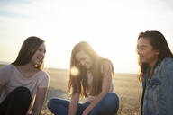 Happy female friends sitting on land against sky - CAVF67723