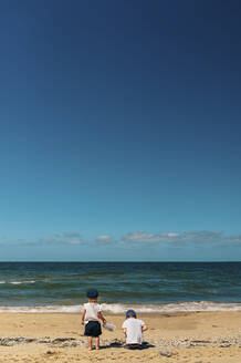 Rear view of siblings playing at beach against blue sky during sunny day - CAVF68075