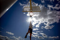 Man playing basketball, dunking against the sun - OCMF00847