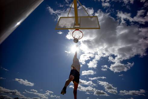 Man playing basketball, dunking against the sun - OCMF00847