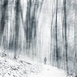 Germany, North Rhine-Westphalia, Wuppertal, Lone hiker standing in snow-covered forest during snowfall - DWIF01069