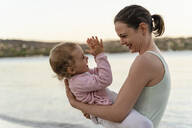 Happy mother carrying her daughter on the beach - DIGF08736