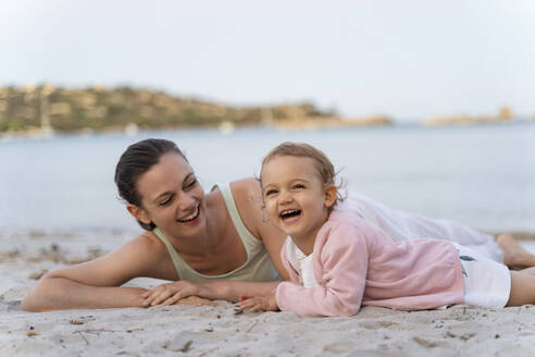 Happy mother with daughter lying on the beach - DIGF08742