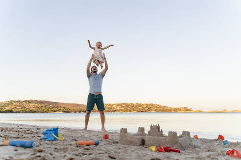 Sand castle and happy father lifting up daughter on the beach - DIGF08754