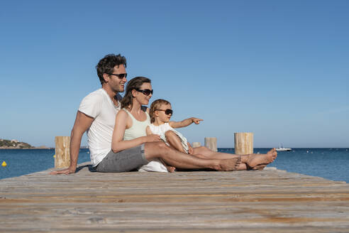 Happy family sitting on a jetty at the sea - DIGF08766