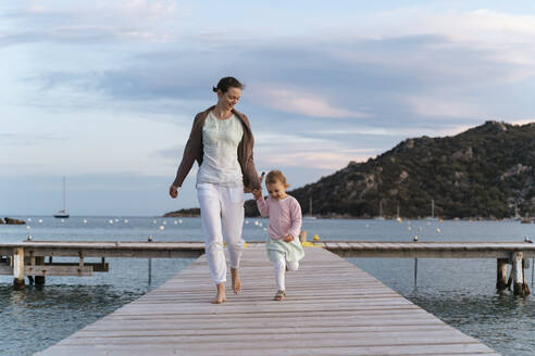 Happy mother with daughter walking on a jetty at sunset - DIGF08775