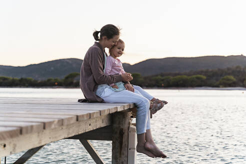 Happy mother with daughter sitting on a jetty at sunset - DIGF08778