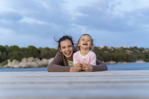Portrait of happy mother and daughter lying on a jetty at sunset - DIGF08784