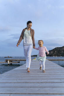 Happy mother with daughter walking on a jetty at sunset - DIGF08790
