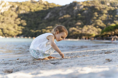 Cute toddler girl playing on the beach - DIGF08793