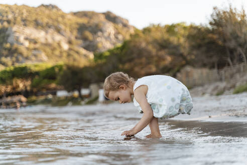 Cute toddler girl playing on the beach - DIGF08799