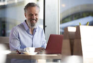 Portrait of happy mature man using laptop in a cafe - FKF03702