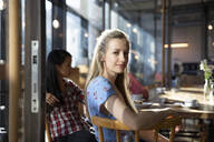 Portrait of confident woman with friends in a cafe - FKF03705