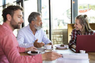 Casual business people having a meeting in a cafe - FKF03711