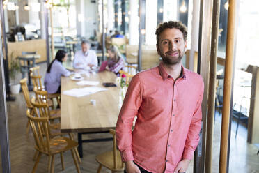 Portrait of casual businessman in a cafe with colleagues having a meeting in background - FKF03714