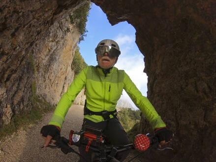 Senior man riding e-bike in nature - LAF02392