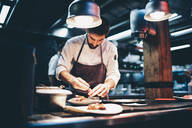 Cook serving food on a plate in the kitchen of a restaurant - OCMF00855