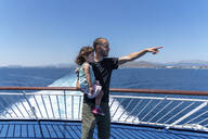 Father standing on the deck of a ship with little daughter on his arm pointing at distance, Mallorca, Spain - GEMF03255