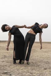 Two women dressed in black performing in bleak landscape - ERRF01932