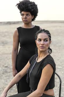 Portrait of two women dressed in black in bleak landscape - ERRF01938