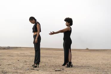 Two women dressed in black standing in bleak landscape - ERRF01944