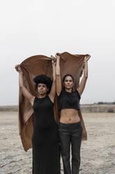 Portrait of two women dressed in black standing together in bleak landscape sharing blanket - ERRF01968