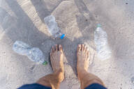 Man's feet on the beach surrounded by empty plastic bottles, top view - DIGF08825