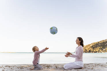 Happy little girl sitting with her mother on the beach playing with Earth beach ball - DIGF08834