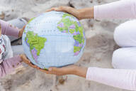 Hands of mother and little daughter holding Earth beach ball, close-up - DIGF08837