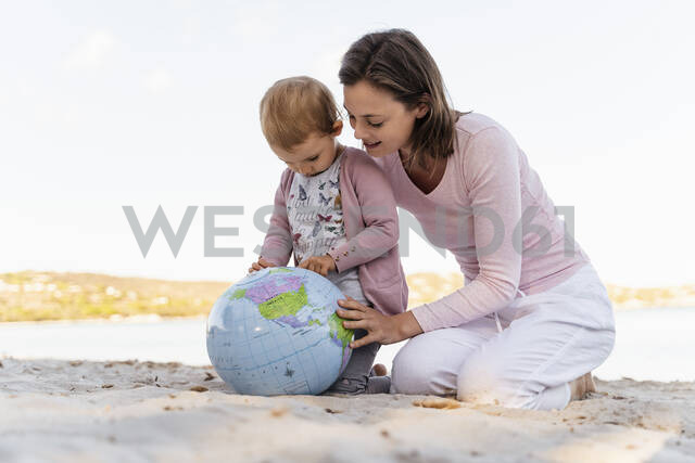Mother and little daughter on the beach looking together at Earth beach ball - DIGF08840 - Daniel Ingold/Westend61