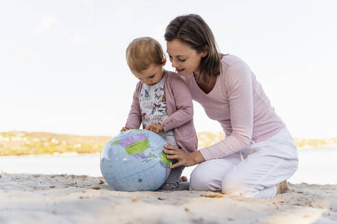 Mother and little daughter on the beach looking together at Earth beach ball - DIGF08840
