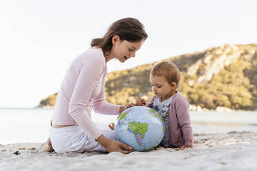 Woman and little daughter sitting on the beach looking together at Earth beach ball - DIGF08843